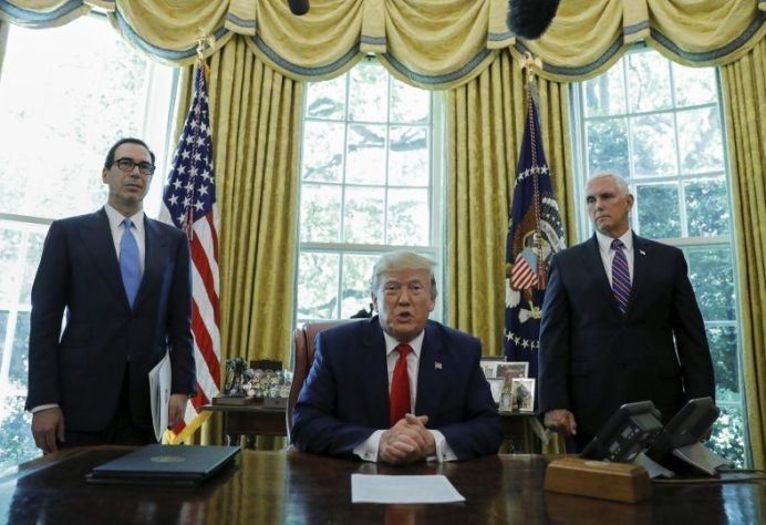 FILE PHOTO: U.S. President Donald Trump speaks before signing an executive order imposing fresh sanctions on Iran as Treasury Secretary Steven Mnuchin and Vice President Mike Pence look on in the Oval Office of the White House in Washington, U.S., June 24, 2019. REUTERS/Carlos Barria