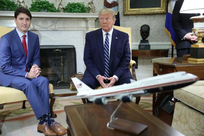 U.S. President Donald Trump and Canada's Prime Minister Justin Trudeau sit behind a scale model of Air Force One as they meet in the Oval Office of the White House in Washington, U.S., June 20, 2019. REUTERS/Jonathan Ernst