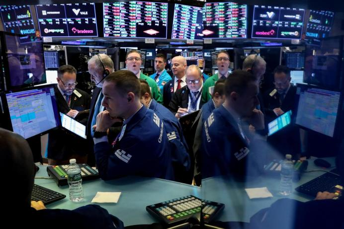 FILE PHOTO: Traders work on the floor at the New York Stock Exchange (NYSE) in New York, U.S .REUTERS/Brendan McDermid