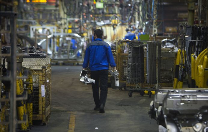 FILE PHOTO: An Iranian worker carries car parts as he walks near a production line of carmaker Iran Khodro, west of Tehran , Iran. Reuters./