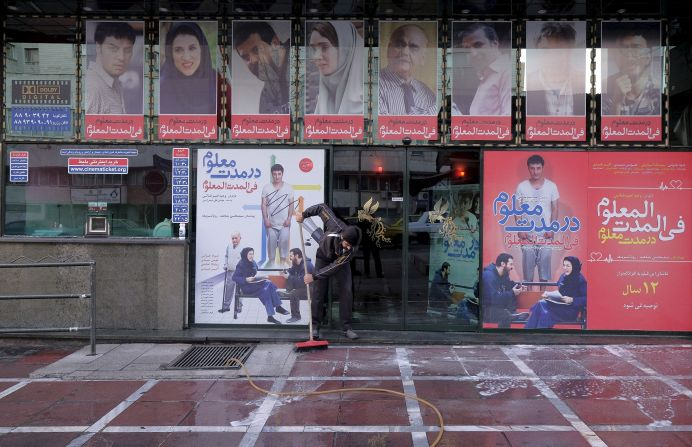 FILE PHOTO: A worker cleans a sidewalk in front of a local cinema in central Tehran January 16, 2016. REUTERS./