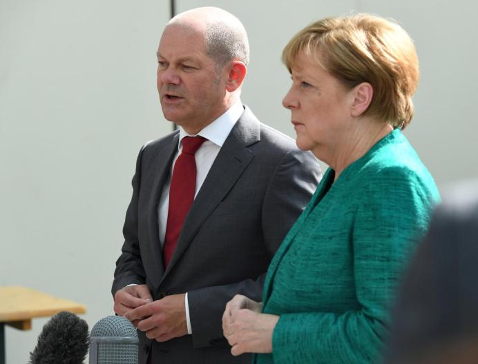 FILE PHOTO: German Chancellor Angela Merkel and Olaf Scholz. REUTERS./