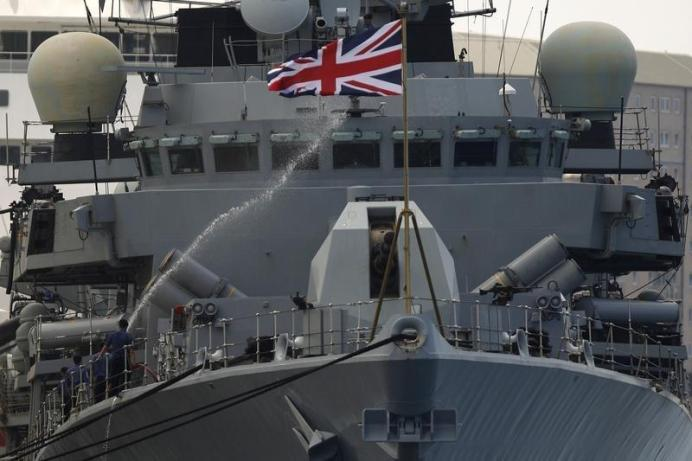 FILE PHOTO: Members of the British Royal Navy frigate HMS Westminster spray water with a hose to clean the ship. REUTERS./