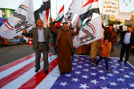 FILE PHOTO: Iraqi people walk on a U.S. flag in a protest after an airstrike at the headquarters of Kataib Hezbollah militia group in Qaim, in the holy city of Najaf, Iraq December 30, 2019. REUTERS/Alaa al-Marjani