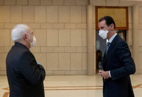 Syria's President Bashar al-Assad and Iran's Foreign Minister Mohammad Javad Zarif, wearing face masks as protection against the spread of the coronavirus disease (COVID-19), meet in Damascus, Syria, in this handout released by SANA on April 20, 2020. REUTERS./