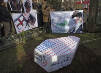 Members of the Basij militia, a part of the Iran Revolutionary Guard, hold anti-U.S. and anti-Israel placards and a picture of Iran's Supreme Leader Ayatollah Ali Khamenei (R), behind a symbolic coffin of the U.S. and Israel during a protest in front of the United Nations' office in Tehran. FILE PHOTO/REUTERS./