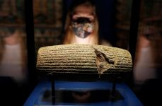 An employee looks at The Cyrus Cylinder, loaned by the British Museum and on display at Epic Iran, an exhibition soon to open at the V&A in London, Britain, May 25, 2021. Picture taken May 25, 2021. REUTERS/Peter Nicholls