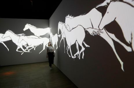 A V&A employee looks at All the White Horses, a hand drawn video animation by Avish Khebrehzadeh, on display in Epic Iran, an exhibition soon to open at the V&A in London, Britain, May 25, 2021. Picture taken May 25, 2021. REUTERS/Peter Nicholls