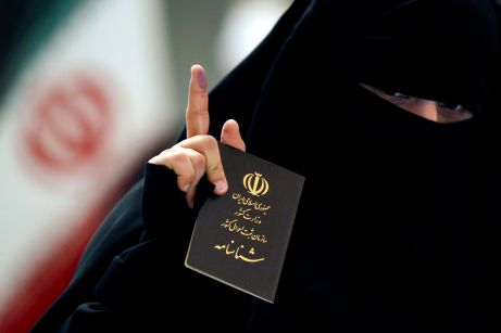 An Iranian woman holds her passport as she shows her ink-stained finger after casting her vote during Iranian presidential election at the Iranian consulate, in Najaf, Iraq, June 18, 2021. REUTERS/Alaa Al-Marjani