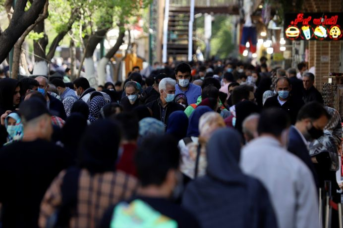 FILE PHOTO: Iranian people wear protective face masks, as they walk amid the spread of the coronavirus disease (COVID-19), in Tehran. REUTERS./