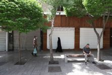 FILE PHOTO: People walk in front of closed shops in Tehran, Iran. REUTERS./