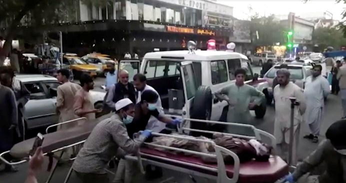 A screen grab shows people carrying an injured person to a hospital after an attack at Kabul airport, in Kabul, Afghanistan August 26, 2021. REUTERS