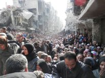 FILE PHOTO: Residents wait to receive food aid distributed by the U.N. Relief and Works Agency (UNRWA) at the besieged al-Yarmouk camp, south of Damascus. REUTERS./
