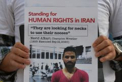 A protester holds posters with Navid Afkari images. Members of the local Iranian diaspora, gathered in front of the Alberta Legislature building during the protest 'Standing for Human Rights in Iran' on the eve of the first anniversary of the execution of Navid Afkari. Navid Afkari was an Iranian wrestler who was sentenced to death and executed after having been falsely accused and convicted of murdering a security guard during the 2018 Iranian protests. On Saturday, September 11, 2021, in Edmonton, Alberta, Canada. (Photo by Artur Widak/NurPhoto)/REUTERS./