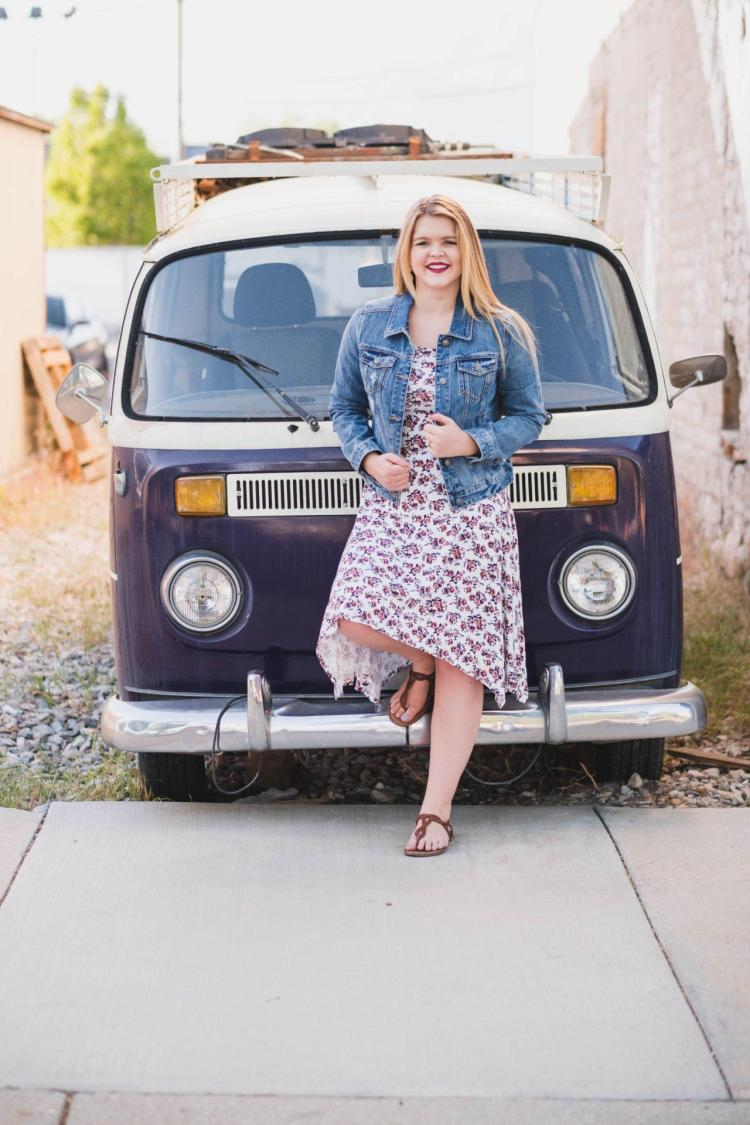 wearing a denim jacket in front of a VW bus