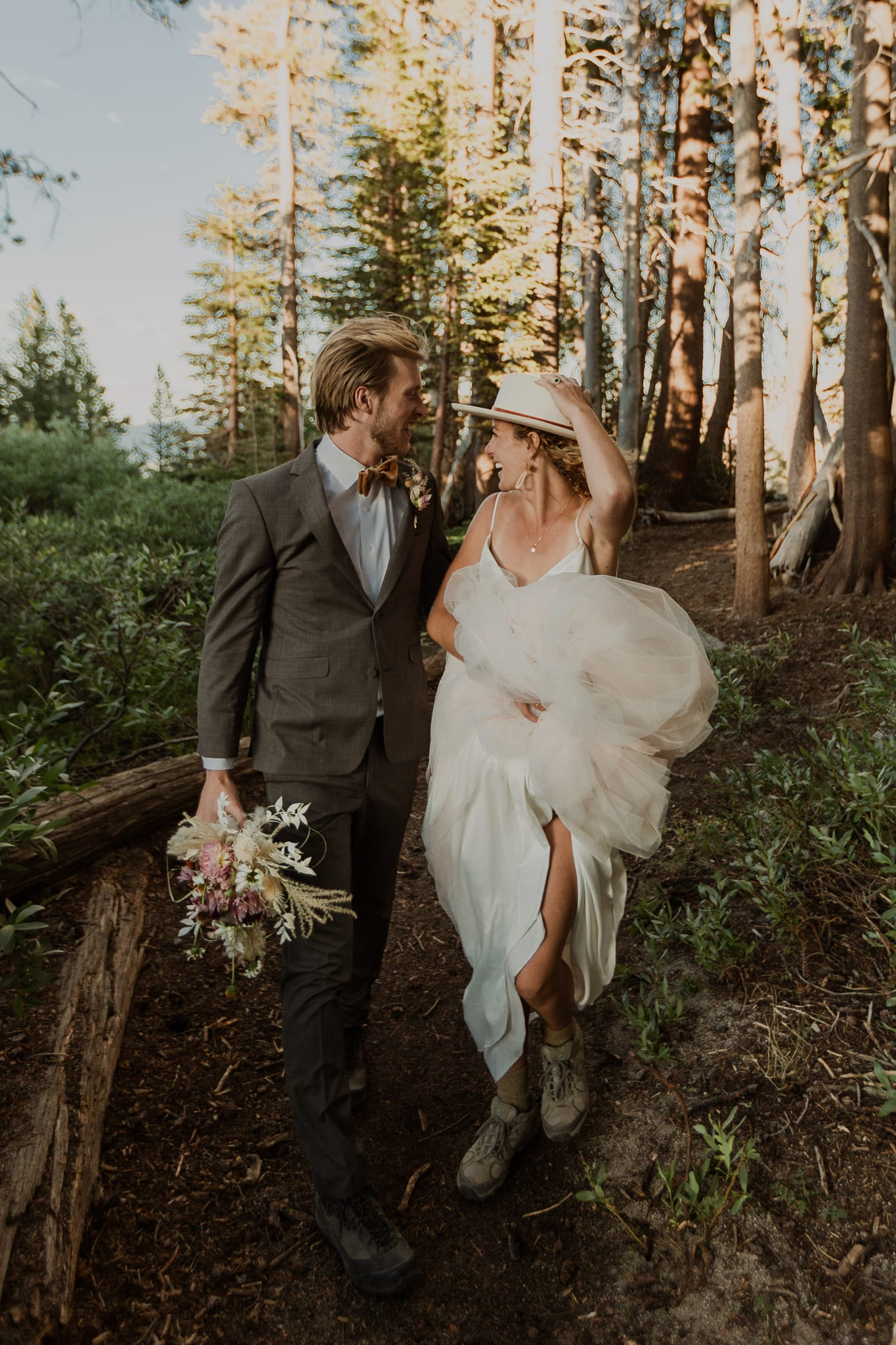 Haylee holds her dress and hat as her and Tyler hike through the Inyo National Forest.