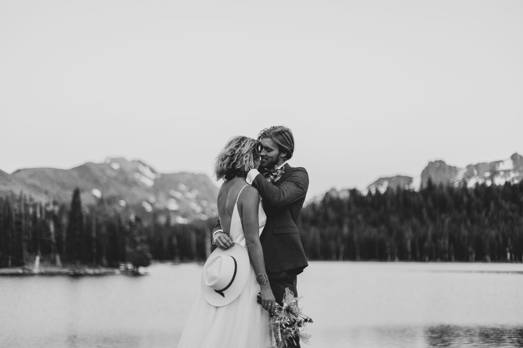 Tyler pulls Haylee close to kiss her on the side of her head on their adventurous elopement day at Mammoth Lakes.