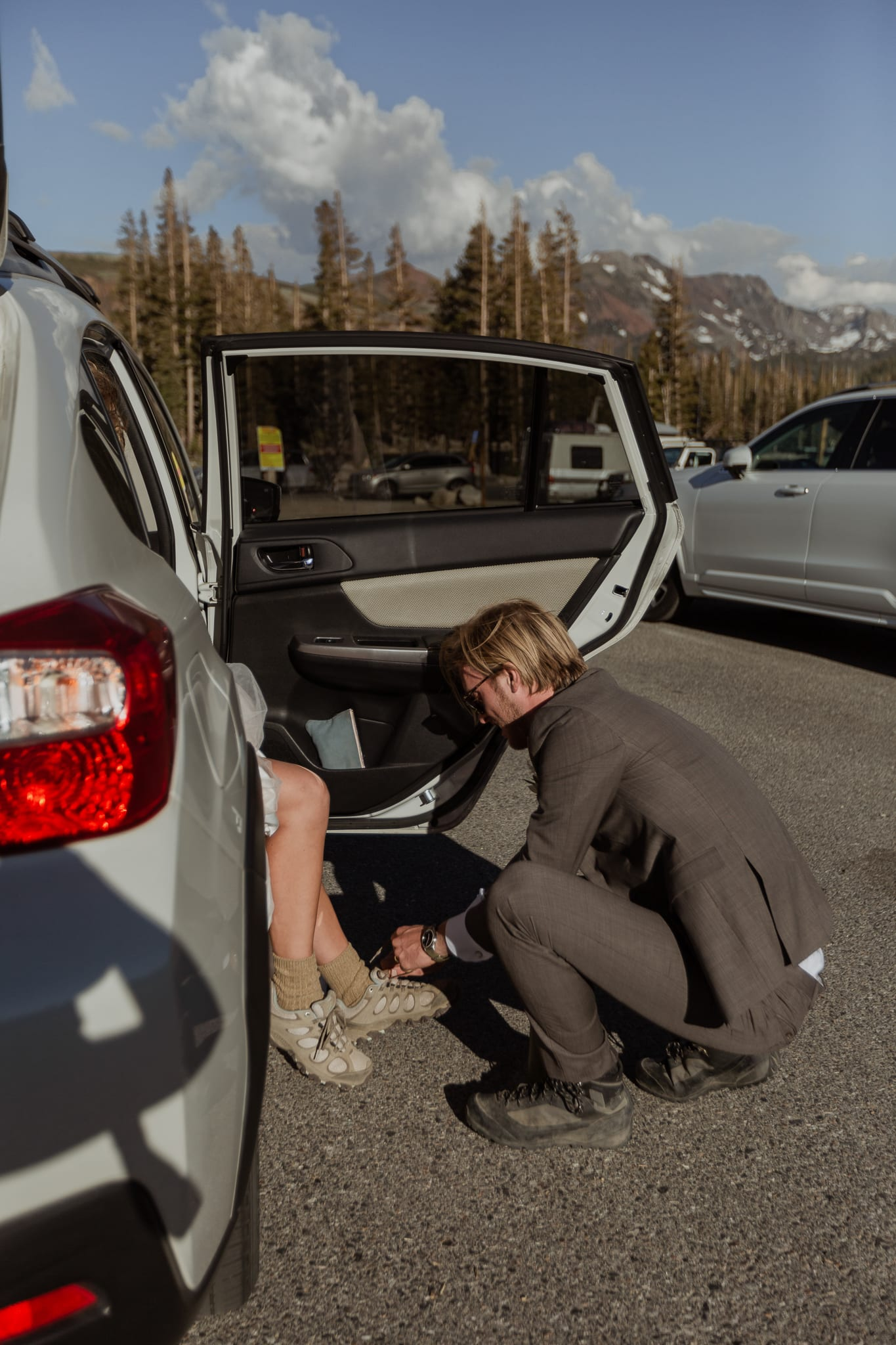 Tyler helps Haylee by tying her hiking boots while she sits with her elopement wedding dress on. They are getting ready to hike up to McLeod Lake.