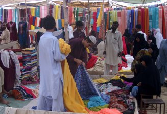 Pushtoon (Pukhtoon) Vendors of Cloths showing different pieces of Cloths on demands of Women in Sunday Bazar (Market), Photo by Yasir Kazmi, Karachi, Pakistan.