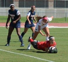 UT-Martin goalie Mariah Klenke (in red) dives for a ball in front of teammates Lucy Pater (16) and Saphyra Coombs-James (13) and Missouri's Allie Hess (22) and in a matchup against Missouri on Sunday, Sept. 7, 2014, at Walton Stadium in Columbia, Missouri. Klenke managed eight saves on the day, but allowed one goal to take the loss. (Tim Leibel)
