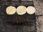 Heating the tortillas alongside the roasted meat.