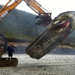 A crew from Leisure Excavating in Florence remove an un-powered boat from the beach at Muriel O. Ponsler Wayside, 13 miles north of Florence.  The boat is possibly debris from the March 2011 tsunami in Japan. (Oregon Parks and Recreation Photo)