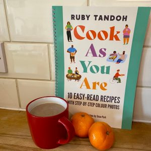 The easy read version of cook as you are, propped up, with a mug of clementine hot chocolate and some clementines in front of it
