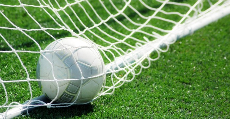 File photo of a soccer ball in the back of a goal net.