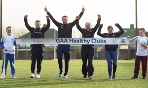 """Ambassadors Philly McMahon, Michael Fennelly, Mickey Harte, and Dr. Aoife Lane, crossing the """"finish line"""" held by students Abbey Mahoney and Jamie Smyth, at the GAA Healthy Clubs launch at Craobh Chiarain GAA Club, Parnell Park in Donnycarney, Dublin."""