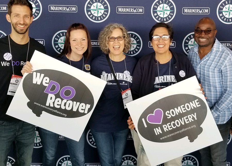 Five KCRC folks at the Seattle Mariners event, holding recovery signs