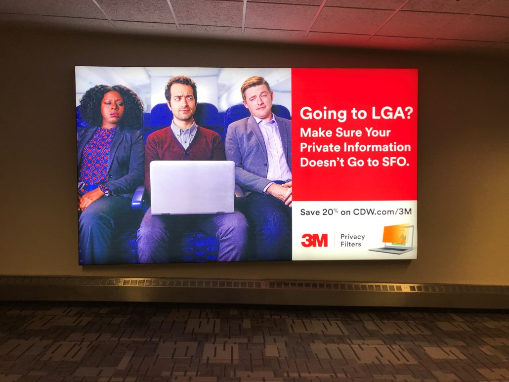 "Photo of a 3M Privacy Airport Display with the headline ""Going to LGA? Make sure your private information doesn't go to SFO."""