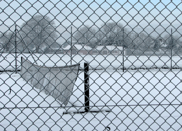 A tennis net blowing in the breeze with snow lying on the ground