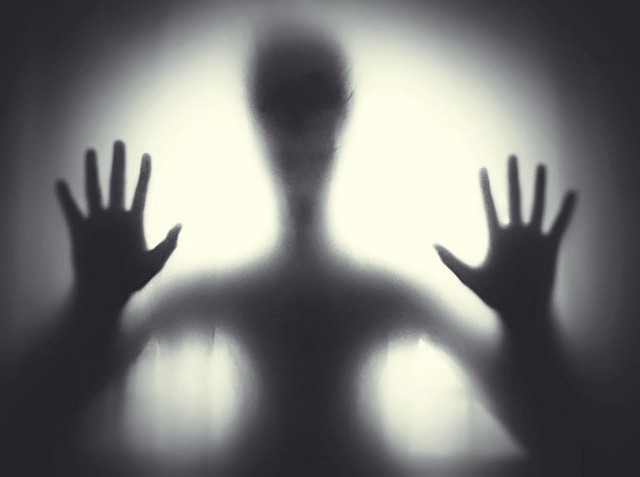 A ghostly full front figure in black and white.