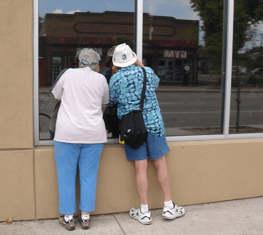 An old couple prying into a darkened shop window