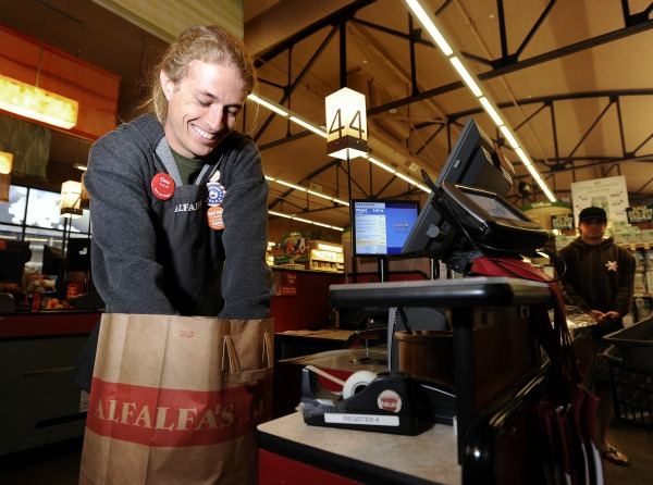 Chris Koury puts groceries in a paper bag for a customer while working the cash register at Alfalfa's Market on Broadway in May. Boulder is considering a 10-cent fee on all disposable grocery bags, paper or plastic. (Jeremy Papasso / Daily Camera file photo)