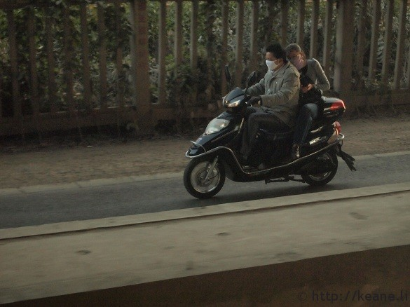 Girl on phone while riding on the back of a scooter in Kunming