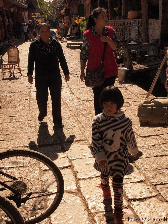 Little Chinese girl in cute outfit in Lijiang Old Town