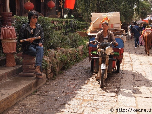Store worker in leather and a traditionally dressed Lijiang driver in Shu He