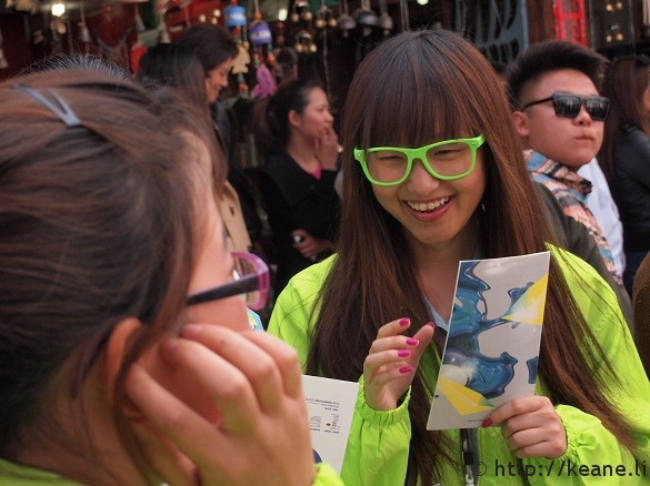 Cute Chinese girl in neon glasses prepares for the COART festival in Lijiang's Shu He Ancient City