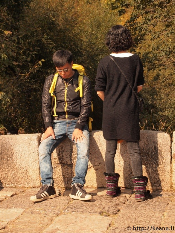Couple with hip shoes inadvertently post on Qinglong Bridge in Shu He Ancient Town