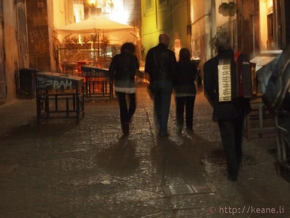 Accordion player walks home along Via Port'Alba in Naples