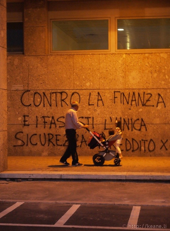 Political graffiti and family in Rimini's Centro Storico at night