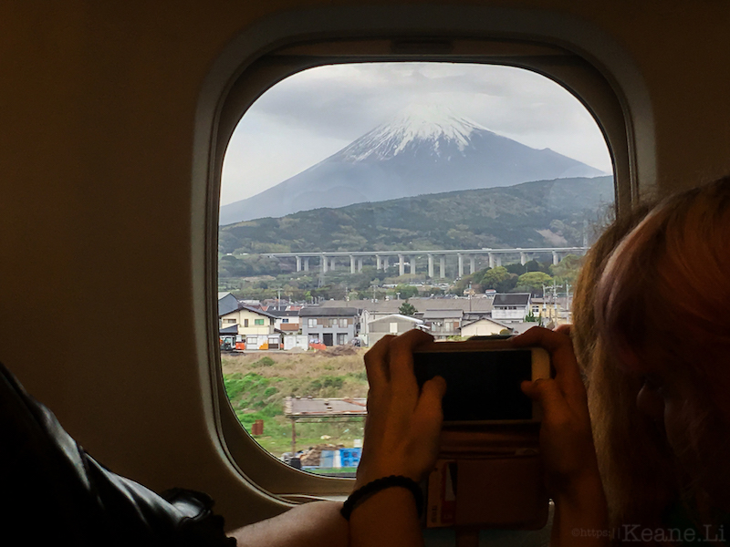 Girl on Shinkansen takes photo of Mt. Fuji