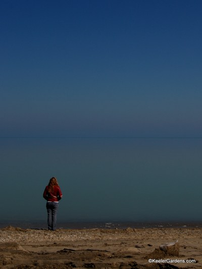 A lone visitor to a somewhat rocky beach in Lake Bluff, IL stands near the water's edge on peers out to an apparently infinite expanse that is Lake Michigan that at some point meets the sky in a thin blue line.