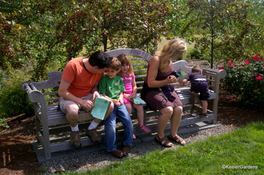 Two adults sit on a bench in a display garden with three children. The man works with a boy and girl of 5 and 6 years old. The women with her camera keeps an eye on the 3 year old who is more interested in climbing the bench.