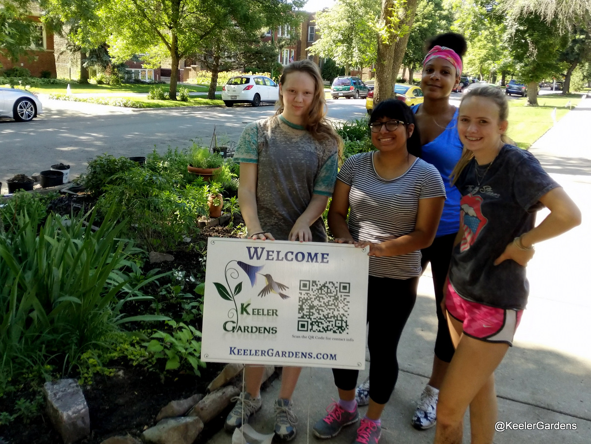 """Four high school interns from across Chicago pose for a picture, standing in the right foreground in a group on a sidewalk with a sign that reads """"Welcome, Keeler Gardens."""" In the background, mostly to the left, is the Keeler Gardens educational pollinator habitat, freshly planted, with a variety of Illinois native pollinator plants."""
