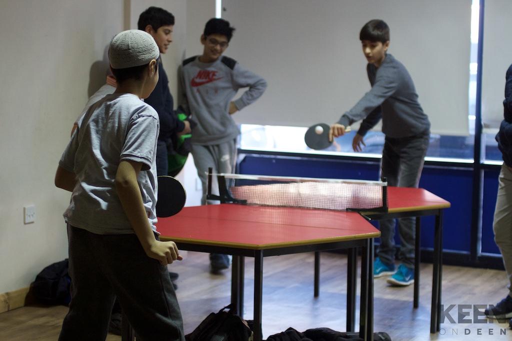 2 boys playing ping pong