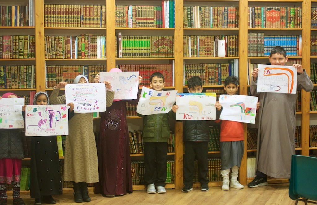 group of students holding up posters they drew