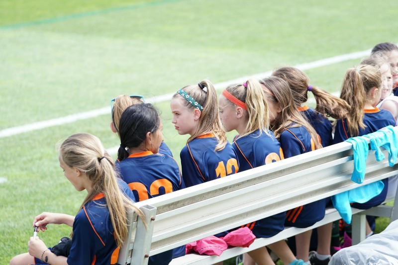 Sports girls sitting on sidelines.