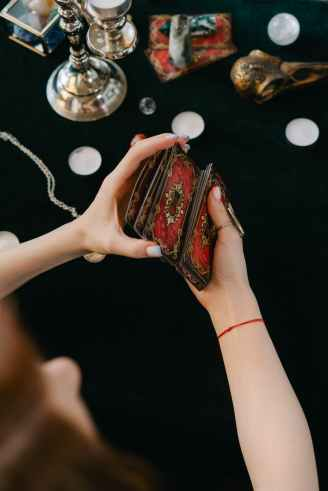 anonymous female fortune teller shuffling tarot cards at table